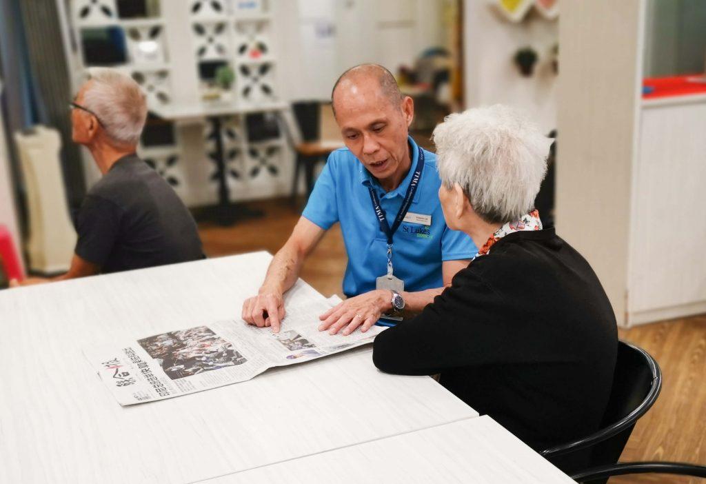 A Heart for Service: Francis reading a mandarin newspaper to an elder